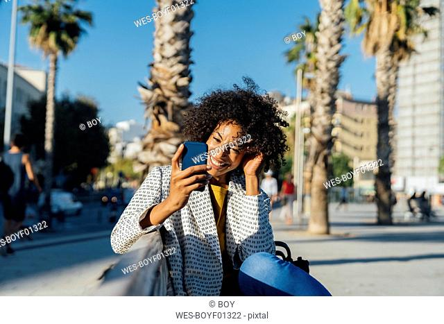 Beautiful woman sitting on a bench in the city, using smartphone