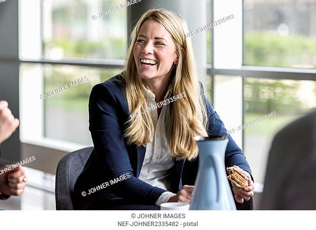 Laughing woman having sandwich