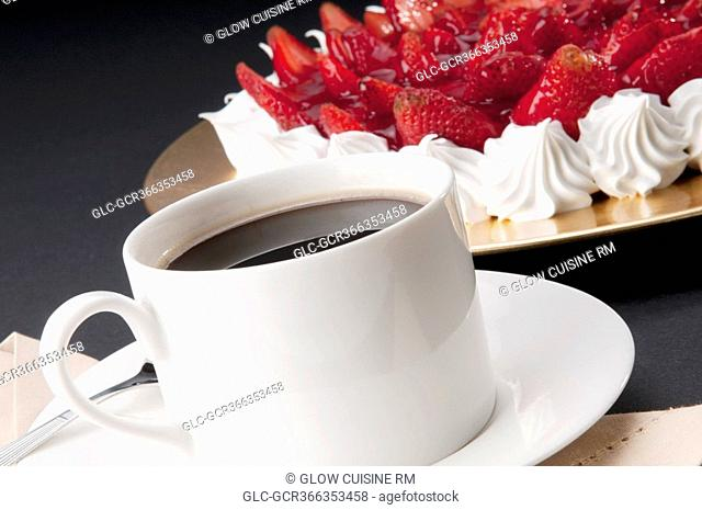 Close-up of strawberry meringue with a cup of black coffee