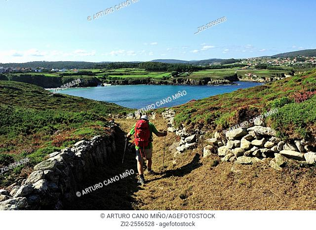 A hiker on the Camiño dos Faros Way of the Lighthouses, in the background it is the beach of Beo. Malpica de Bergantiños, La Coruña, Spain