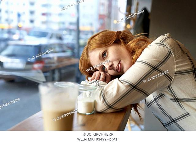 Daydreaming young woman in a cafe