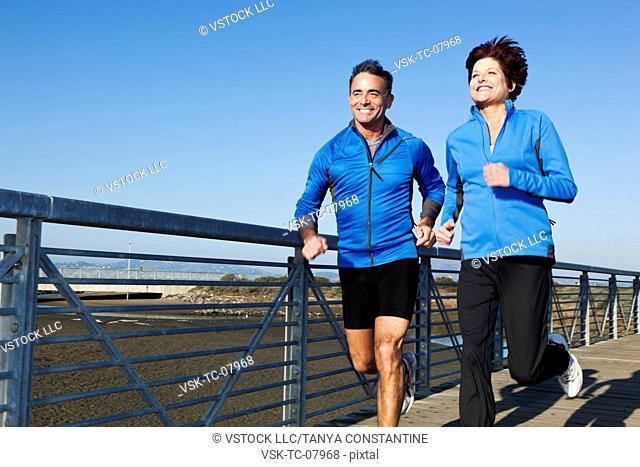 USA, California, San Francisco, Senior couple jogging on boardwalk