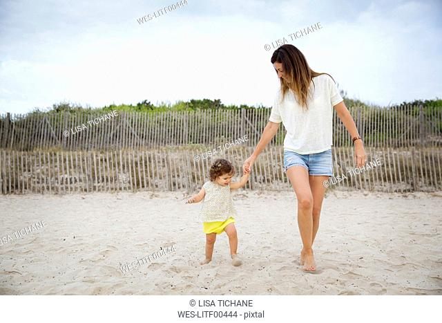 Mother with little daughter walking on the beach