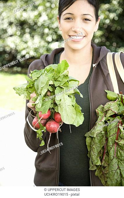 Hispanic woman holding bunch of radishes