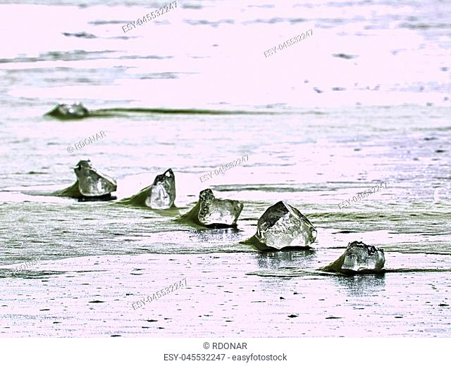 sparkling shards of cracked ice jut out on the frozen lake. The light effect occurs in deep and shallow cracks of sublime ice