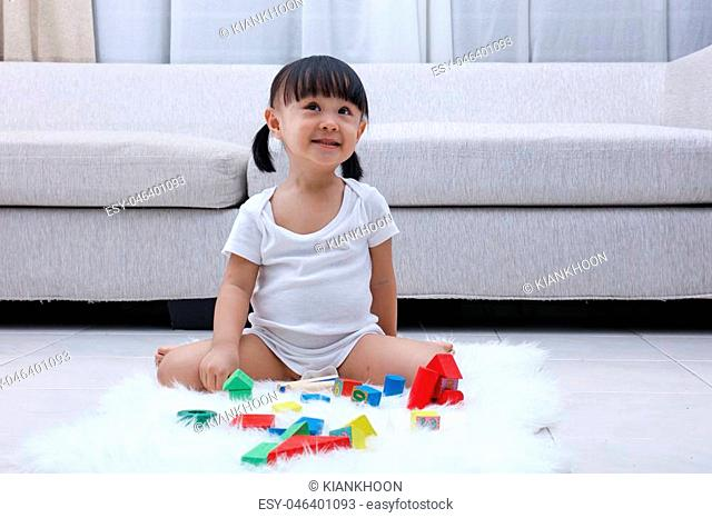Happy Asian Chinese little girl playing blocks on the floor in the living room at home