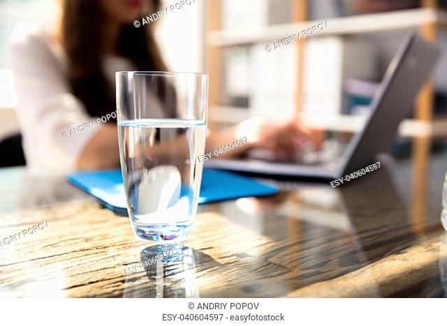 Glass Of Water In Front Of Businesswoman Using Laptop