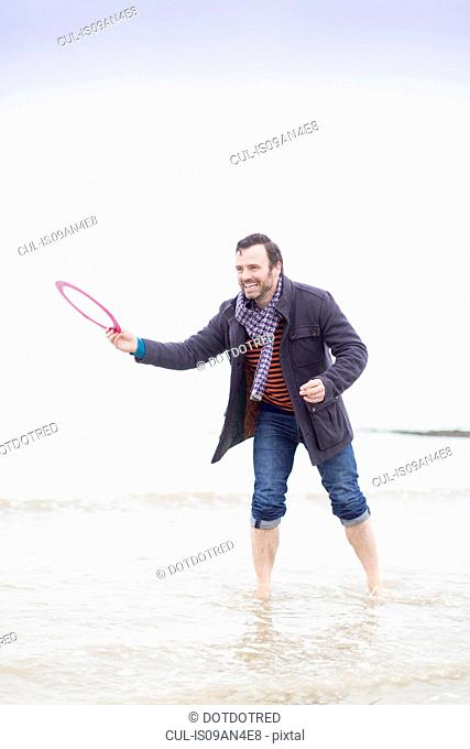 Mature man standing in sea, holding frisbee