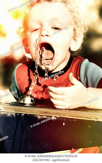 Thirsty young blond 3 year old child catching water splash in mouth during a hot Australian summer