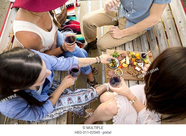Friends drinking red wine and enjoying charcuterie board at picnic table