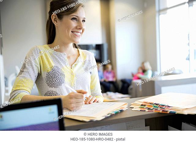 Confident receptionist writing on medical record