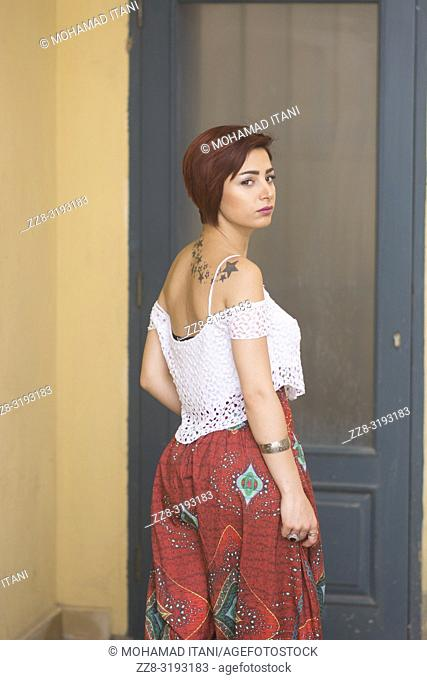 Beautiful young woman with short red hair looking over shoulder by the door