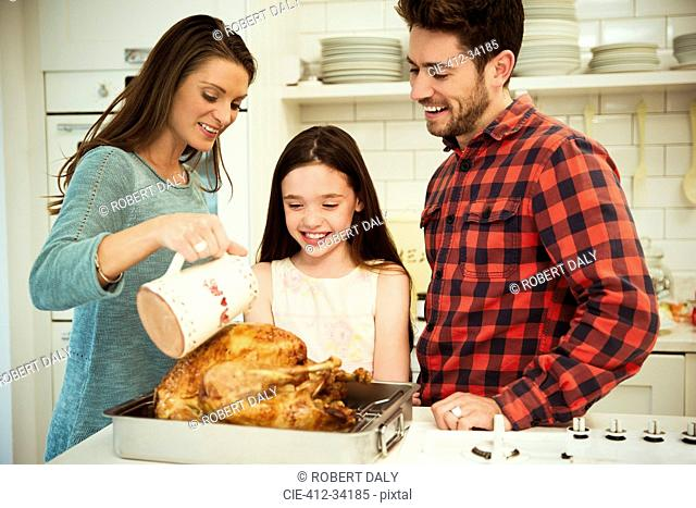 Family preparing Christmas dinner turkey in kitchen