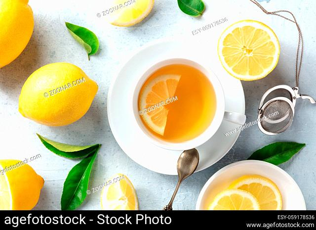 Lemon tea in a cup, overhead flat lay shot with organic lemons and green leaves. Tasty citrus detox drink, natural remedy