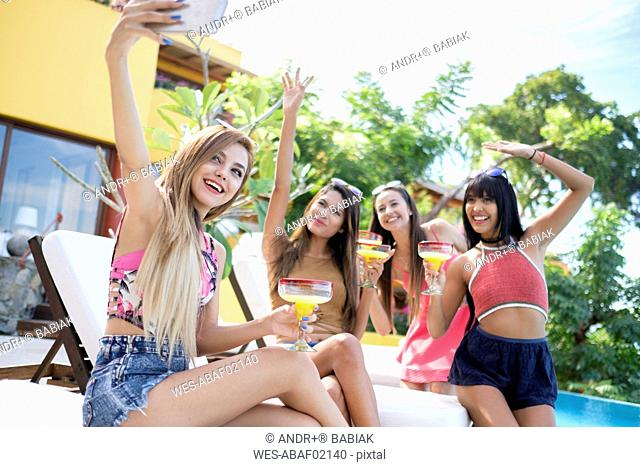 Young woman taking selfie with friends at the poolside