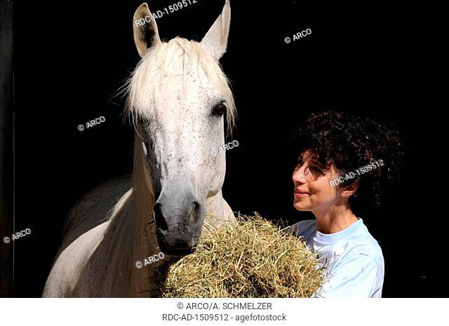 Feeding Hay, woman feeding horse
