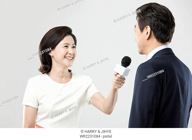Woman in formal wear putting a microphone close to a man in suit