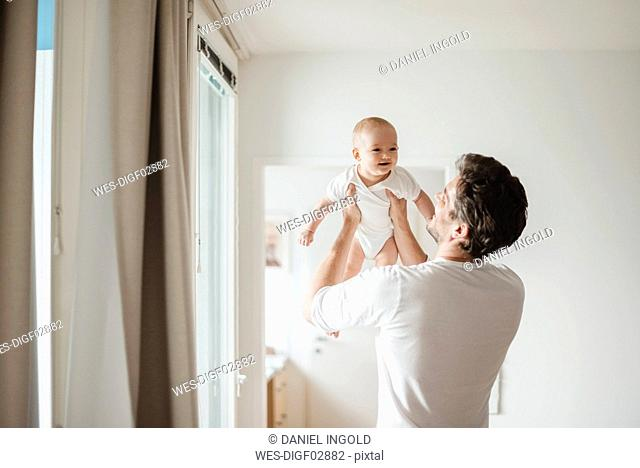 Father holding baby girl at home