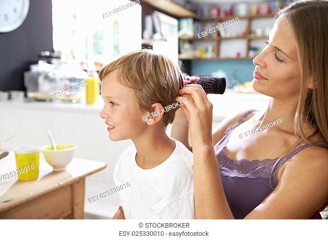 Mother Brushing Son's Hair At Breakfast Table