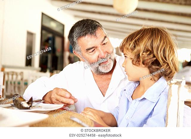 Grandfather And Grandson Enjoying Meal In Restaurant