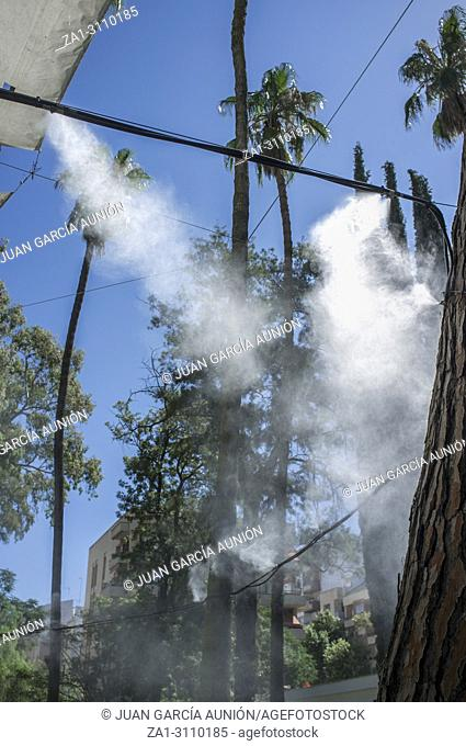 Awning and sprinklers splashing vaporized water at public park. Devices for cooling the hot summer temperature in Spain outdoors
