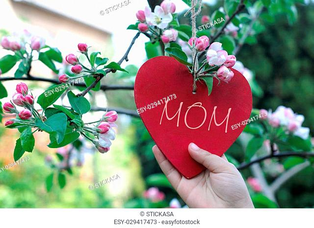 Child Hanging Heart on Branch in Bloom - Mother's Day Concept