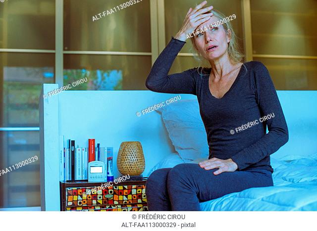 Mature woman sitting on bed with hand on forehead and upset expression on face