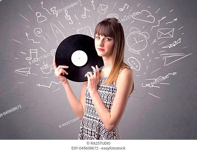 Young lady holding vinyl record on a grey background with mixed scribbles behind her