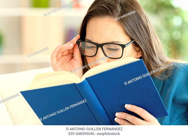 Woman suffering eyestrain reading a book wearing eyeglasses at home