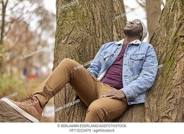 man sitting at tree, in Englischer Garten in Munich, Germany