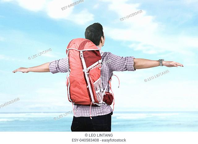 Back view of asian tourist relax and enjoying seascape with blue sky background