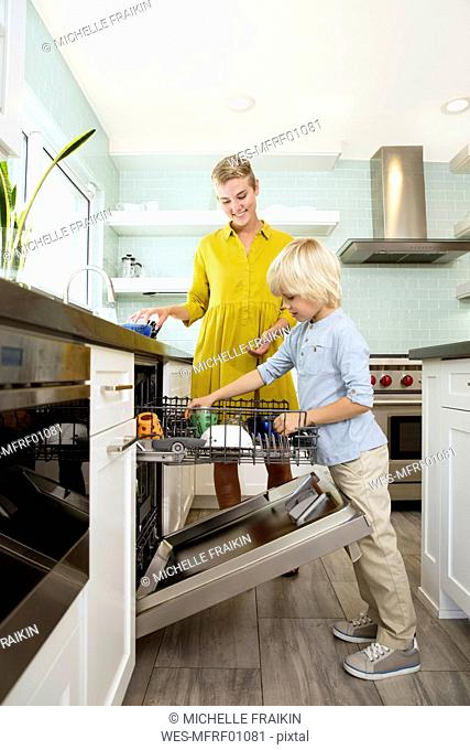 Boy helping mother clearing the dishwasher in kitchen