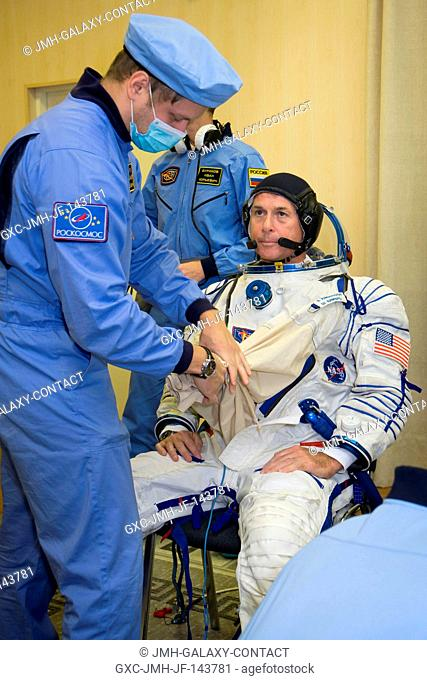 Expedition 49 flight engineer Shane Kimbrough is helped into his Sokol launch and entry suit in preparation for conducting the first check dress rehearsal...