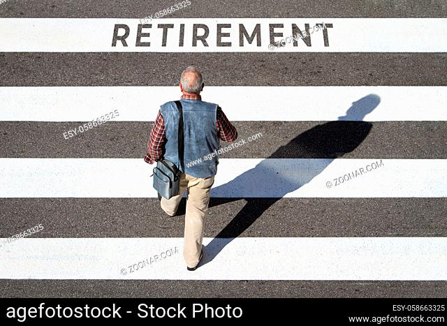 Retirement concept. Scene of a senior man walking in a cebra crossing towards retirement text. Top view