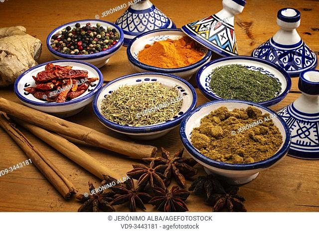 Healthy food. Spices in ceramic containers typical of Morocco on an old wooden table. Colored pepper, curcuma, cayenne, cinnamon, ginger, cumin, star anise