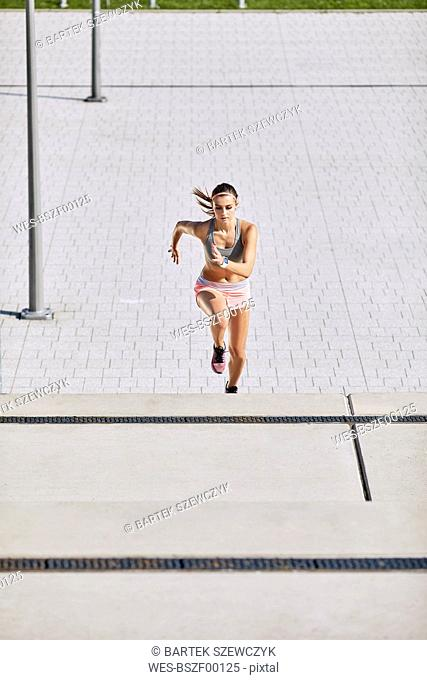 Fit young woman running on stairs