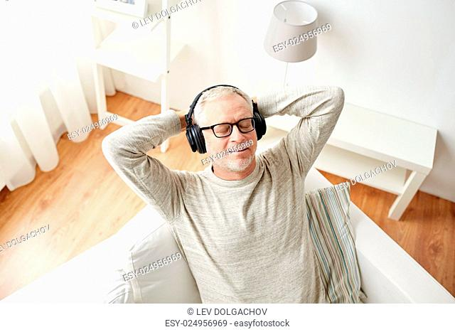 technology, people and lifestyle concept - happy senior man in headphones listening to music at home