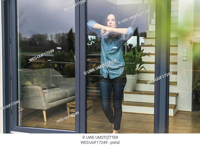Serious woman standing behind terrace door at home