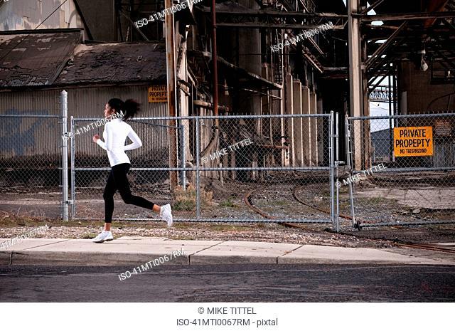 Woman running on industrial city street