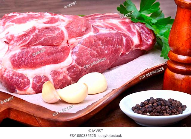 Raw pork neck chop meat with parsley herb leaves, grinder for spices and garlic on a stone background. Ready for cooking