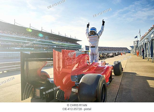 Formula one race car driver cheering on sports track, celebrating victory