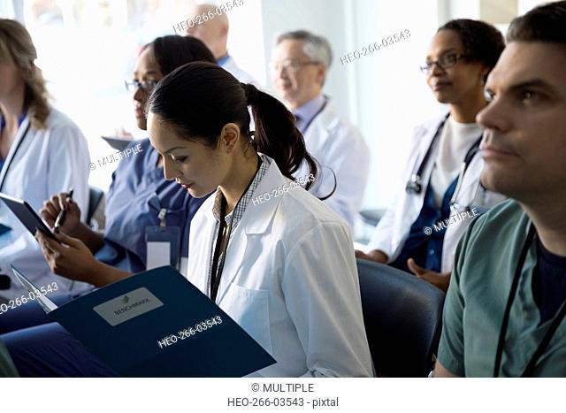Doctor reading paperwork in seminar audience