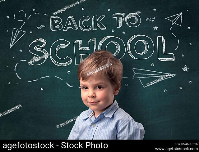 Adorable little boy with blackboard and back to school concept