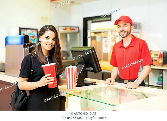 Gorgeous brunette holding a bag of popcorn and a soda next to a concession stand in a movie theater
