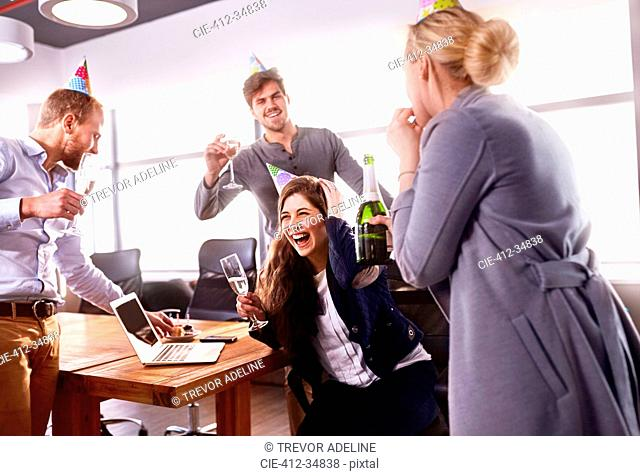 Business people drinking champagne, celebrating birthday in conference room