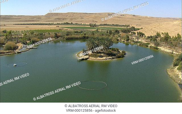 Aerial footage of a lake in the Negev Desert. Oasis in the middle of the desert, palms and agricultural fields