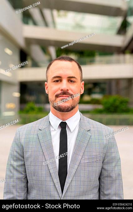 Portrait of handsome Hispanic bald bearded businessman wearing suit in the city streets outdoors