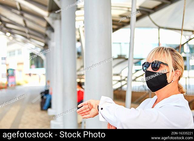 Pendlerin mit Gesichtsmaske wegen Covid-19 im Nahverkehr wartet auf den Bus