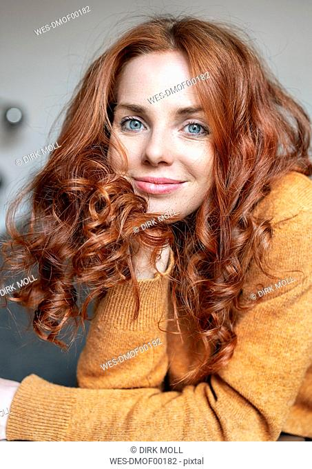 Close-up portrait of beautiful redhead woman at home