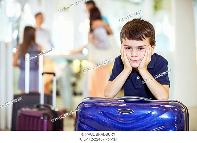 Portrait of pensive boy leaning on suitcase in hotel lobby